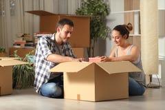 Пожитки серьезных пар кладя в коробку на доме пола двигая стоковое фото