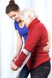 Пожилая дама идя на костыли стоковая фотография