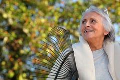 Пожилая дама сгребая листья стоковые изображения