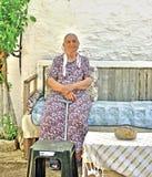 Пожилая дама сидя в ее саде стоковые фото