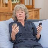 Пожилая дама с 2 smartphones Стоковое Фото