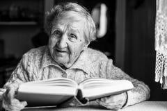 Пожилая дама читая книгу, сидит на таблице Стоковое Изображение RF