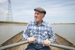 Пожилая весельная лодка человека Стоковые Изображения RF