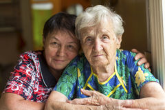 Пожилая женщина, взрослая дочь обнимая позади Стоковое Фото