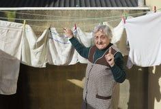 Пожилая женщина вися вне стирку Стоковые Фотографии RF