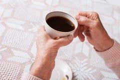 Пожилая женщина выпивает чай дома Старшая женщина держа чашку чаю в их руках на крупном плане таблицы Горизонтально верхняя часть Стоковая Фотография