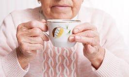 Пожилая женщина выпивает чай дома Старшая женщина держа чашку чаю в их руках на крупном плане таблицы Стоковая Фотография