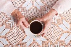 Пожилая женщина выпивает чай дома Старшая женщина держа чашку чаю в их руках на крупном плане таблицы Горизонтально верхняя часть Стоковые Фото