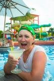 Пожилая женщина выпивает mojito в бассейне Стоковое Изображение
