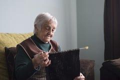 Пожилая женщина вязать дома Стоковые Изображения RF