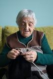 Пожилая женщина вязать дома Стоковые Изображения