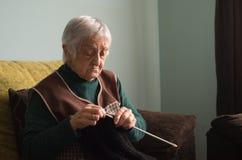 Пожилая женщина вязать дома Стоковое Изображение