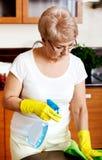 Пожилая женщина в желтых перчатках очищая таблицу Стоковые Фото