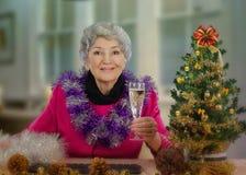Пожилая женщина в розовой куртке провозглашать с Рождеством Христовым Стоковые Фотографии RF
