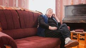 Пожилая женщина говоря на мобильном телефоне около рояля Стоковые Фото