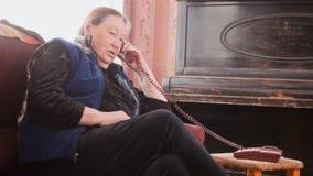 Пожилая женщина говоря на телефоне дома Стоковая Фотография