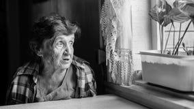 Пожилая женщина горюет около окна Стоковое Изображение