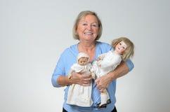 Пожилая женщина держа 2 античных куклы Стоковые Фото