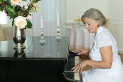 Пожилая женщина играя рояль дома Стоковое фото RF