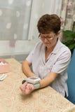 Пожилая женщина измеряет давление стоковая фотография