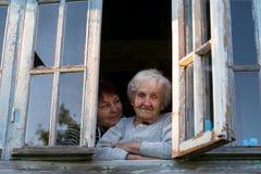 Пожилая женщина и ее взрослая дочь смотря вне окно Стоковое фото RF