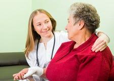 Пожилая женщина и молодой доктор Стоковая Фотография