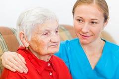 Пожилая женщина и молодой человек осуществляющий уход Стоковые Изображения