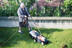 Пожилая женщина которая режет траву в саде Стоковое Фото