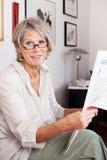 Пожилая женщина наслаждаясь читающ газету Стоковые Изображения RF