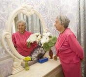 Пожилая женщина около зеркала Стоковое фото RF