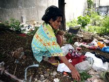 Пожилая женщина охотится или собирать для годных для повторного использования материалов в куче погани в покинутой серии Стоковые Фотографии RF