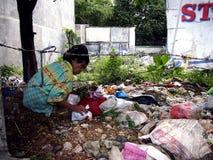 Пожилая женщина охотится или собирать для годных для повторного использования материалов в куче погани в покинутой серии Стоковое Изображение RF