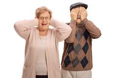 Пожилая женщина покрывая ее уши и пожилой человека покрывая его Стоковые Фотографии RF