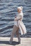 Пожилая женщина представляя с оружиями пересекла на берег реки на дневном времени Стоковая Фотография RF