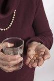 Пожилая женщина принимая ее лекарство Стоковое Изображение RF
