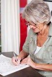 Пожилая женщина разрешая кроссворд Стоковые Изображения RF
