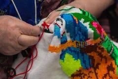 Пожилая женщина сидит ее вышивкой вышивки крестиком Стоковое Изображение RF
