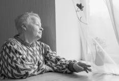 Пожилая женщина сидит и смотрит вне окно Стоковая Фотография RF
