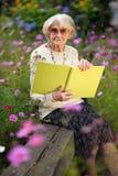 Пожилая женщина сидя в ее саде с книгой Стоковые Фото