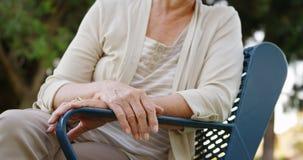 Пожилая женщина сидя на скамейке в парке Стоковая Фотография