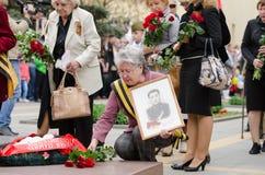 Пожилая женщина с войной фото кладет цветки на памятник Стоковое Фото
