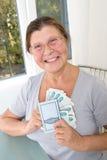 Пожилая женщина с русскими деньгами и сбережения записывают Стоковые Фотографии RF