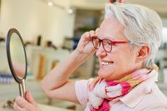 Пожилая женщина с смотреть стекел стоковое фото