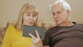 Пожилая пара звенит на видео- связях на таблетке Супруг и жена сидя дома на кресле Концепция  видеоматериал