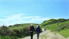 Пожилая пара идет вверх по холму держа руки акции видеоматериалы