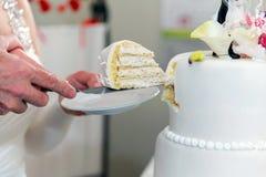 Пожилая пара режет свадебный пирог Стоковое Изображение RF