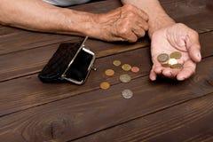 Пожилая персона держит монетки над старым пустым бумажником _ Стоковое Изображение