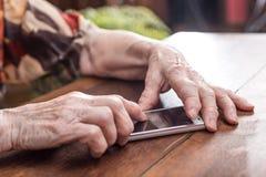 Пожилая персона используя smartphone Стоковое Фото