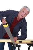 Пожилая древесина sawing разнорабочего стоковая фотография rf