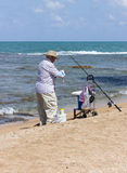 Пожилая рыбная ловля человека с рыболовной удочкой Стоковые Изображения
